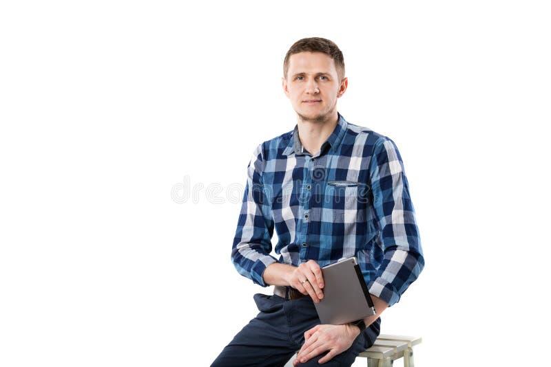 En ung Caucasian man med en minnestavla i hans händer sitter på en vit isolatbakgrund Temastående av en man, royaltyfria bilder