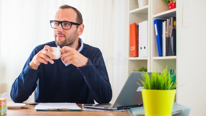 En ung caucasian man som dricker kaffe i hans kontor. royaltyfri foto