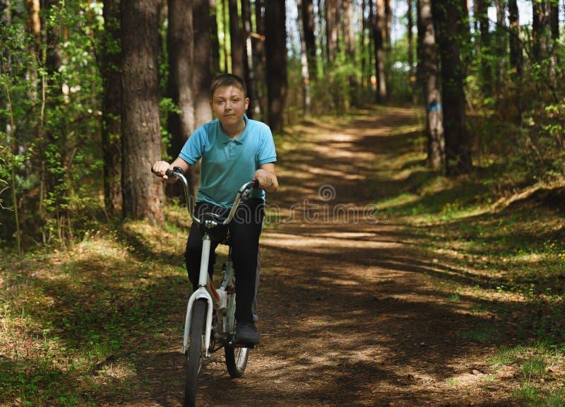 En ung caucasian pojke rider cykeln p? en solig dag arkivbilder