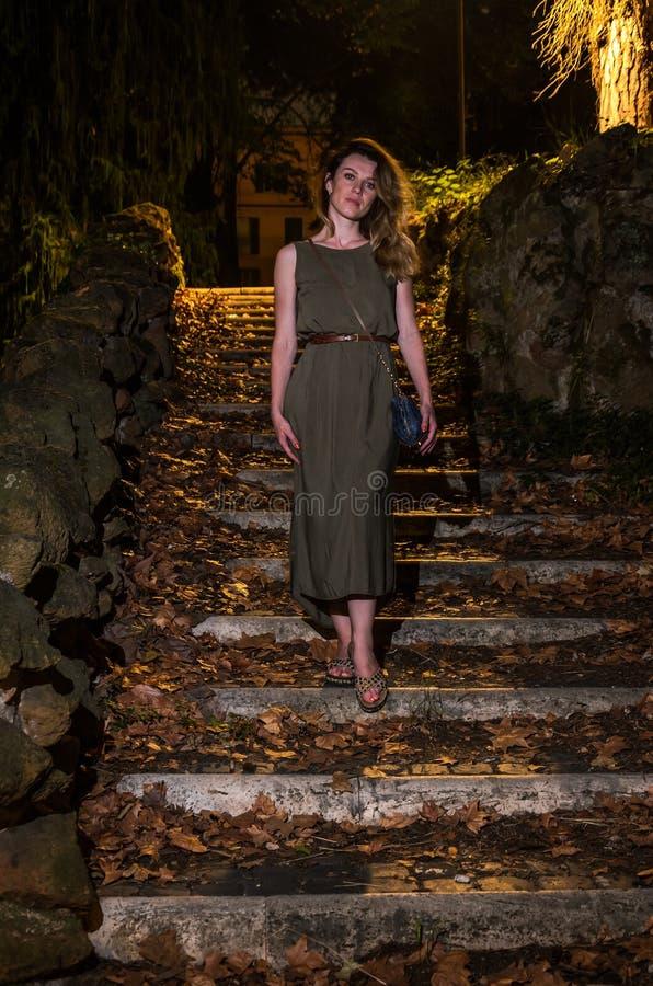 En ung charmig flicka i en klänning klättrar momenten som är upplysta vid en lykta på natten i parkera arkivbild