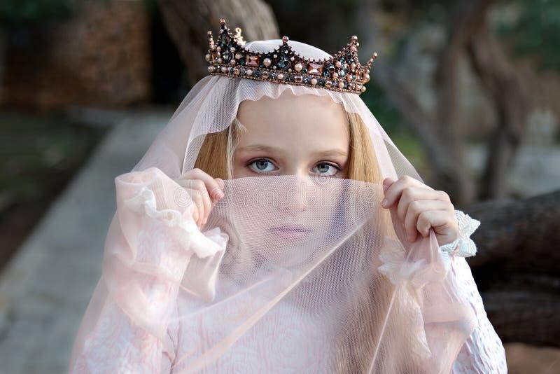 En ung concubineprinsessa i kronaräkningarna hennes framsida med en skyla och blickar reproachfully arkivfoto