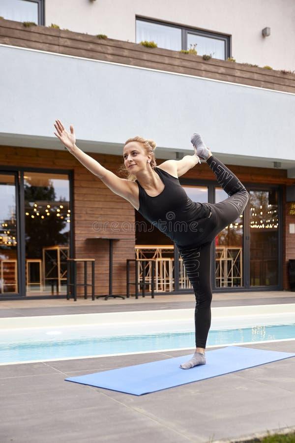 En ung dam, 20-29 år, gammal görande yoga på en yoga som är matt i en trädgård av ett härligt utsmyckat hus fotografering för bildbyråer
