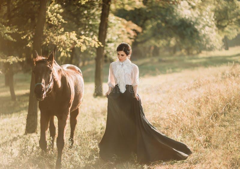En ung dam i en tappningklänning med ett långt drev, går med en häst till och med skoggläntorna En forntida samlad frisyr, royaltyfri fotografi