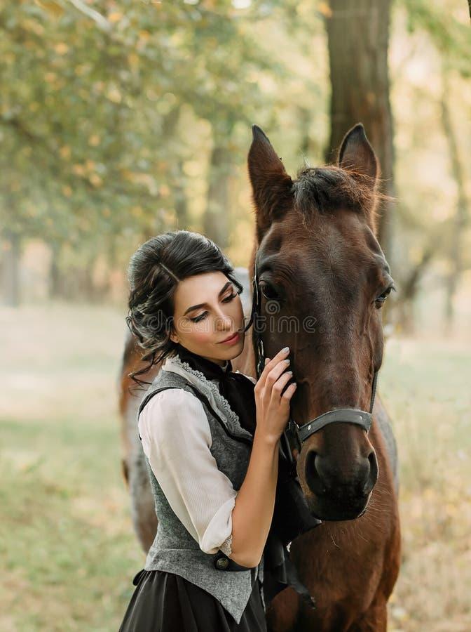 En ung dam i en tappningklänning, med mjukhet och med affektion kramar hennes häst En forntida samlad frisyr, ett försiktigt gör royaltyfria foton