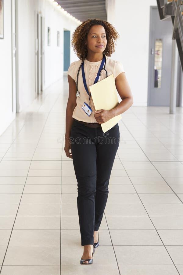 En ung doktor med stetoskopet som går i modern lobby arkivbild