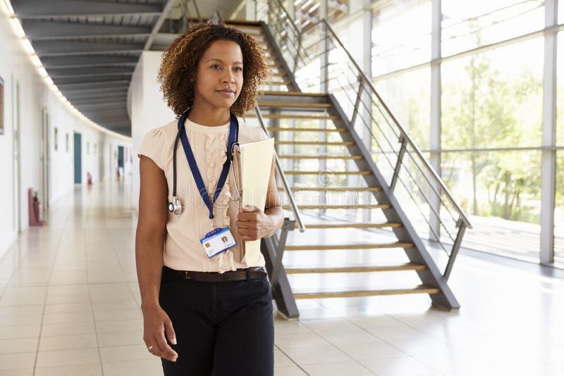 En ung doktor med stetoskopet som går i modern lobby fotografering för bildbyråer