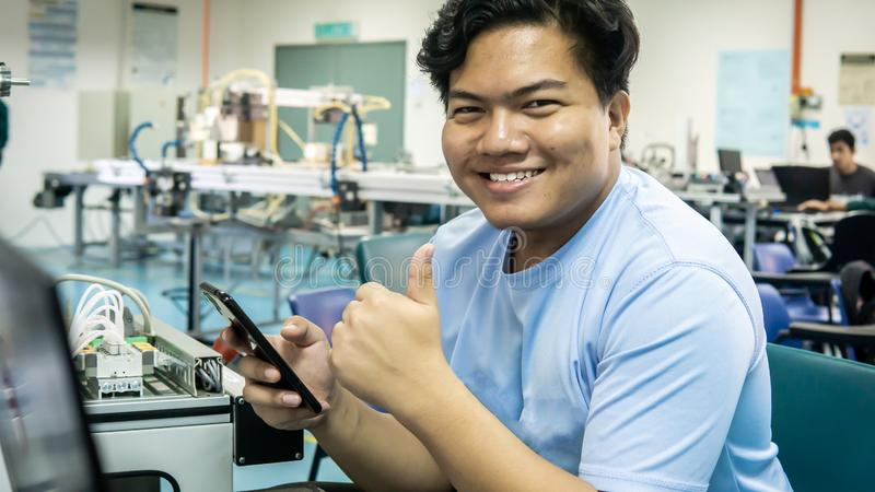 En ung elev på Malay som leker, håller en smartphone och visar tummen arkivbild