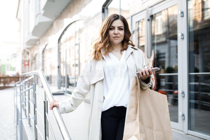En ung förstående kvinna, inte enhövdad kroppbyggnad, går runt om staden med en shoppa påse, rymmer telefonen i henne arkivbild