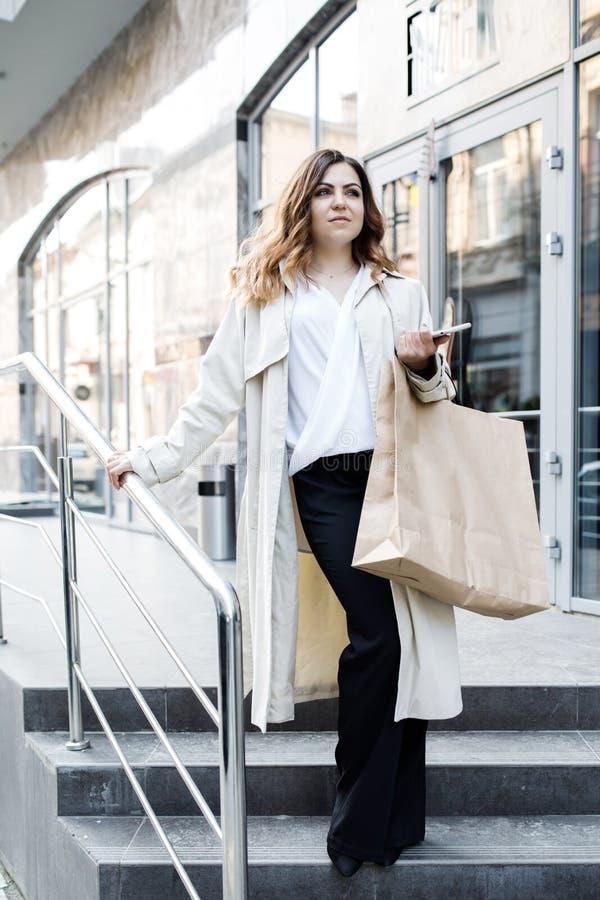 En ung förstående kvinna, inte enhövdad kroppbyggnad, går runt om staden med en shoppa påse, rymmer telefonen i henne royaltyfri foto