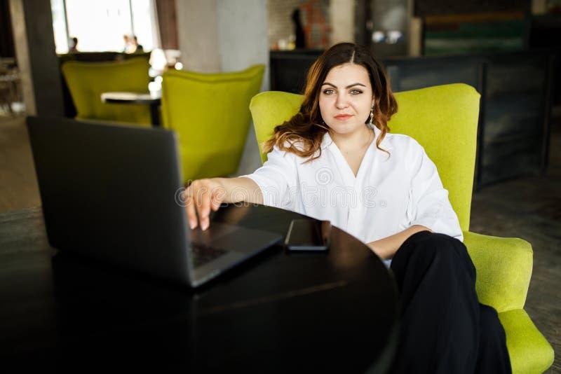 En ung förstående kvinna, inte enhövdad kroppbyggnad, sitter i ett hemtrevligt kafé och arbetar för en bärbar dator Aff?rskl?dsti royaltyfria bilder