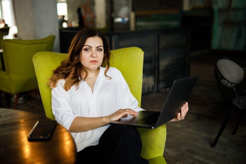 En ung förstående kvinna, inte enhövdad kroppbyggnad, sitter i ett hemtrevligt kafé och arbetar för en bärbar dator Aff?rskl?dsti arkivbild