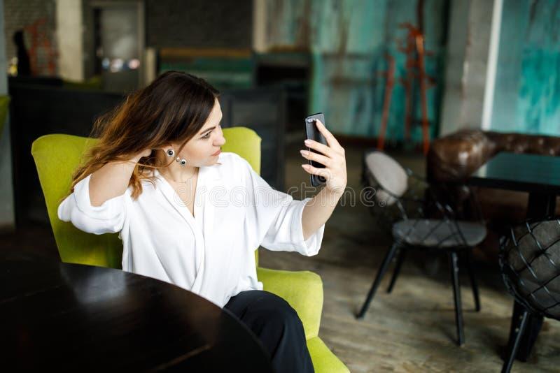 En ung förstående kvinna, inte enhövdad kroppbyggnad, sitter i ett hemtrevligt kafé, rymmer en smartphone i hennes händer och väl royaltyfri bild