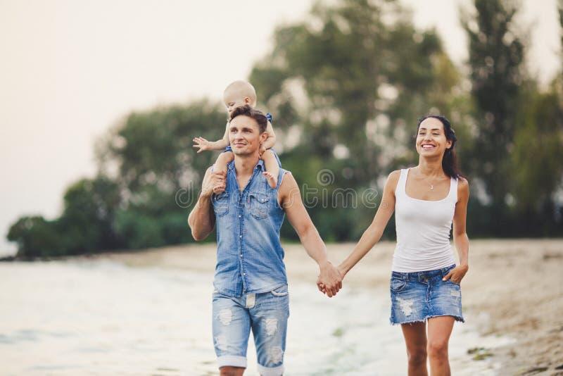 En ung familj av tre promenerar en sandig strand Behandla som ett barn lite flickan med blond som är årig från födelse, sitter på royaltyfria bilder