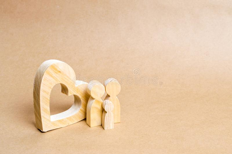 En ung familj med ett barn står nära en trähjärta Förälskelse och lojalitet, en stark ung familj Familjförhållanden arkivfoto