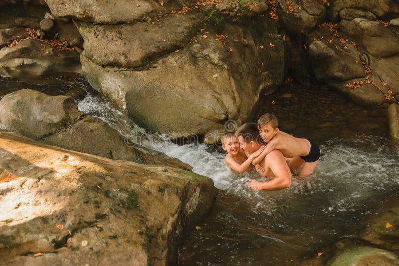 En ung far och hans söner badar i en bergsflod fotografering för bildbyråer