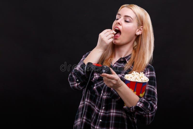 En ung flicka äter popcorn och innehavet en lek av styrspaken fotografering för bildbyråer