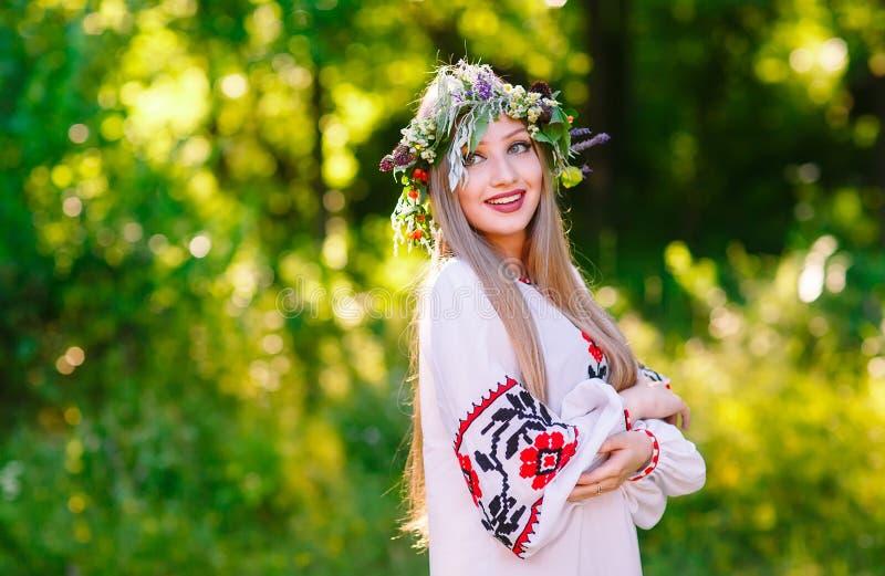 En ung flicka av det slaviska utseendet med en krans av l?sa blommor p? solst?ndet fotografering för bildbyråer
