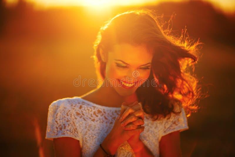 En ung flicka ber på solnedgången royaltyfria foton
