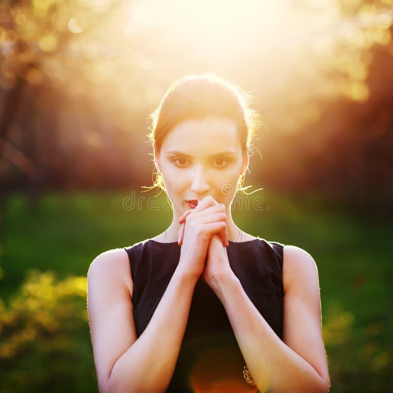 En ung flicka ber på solnedgången arkivfoto