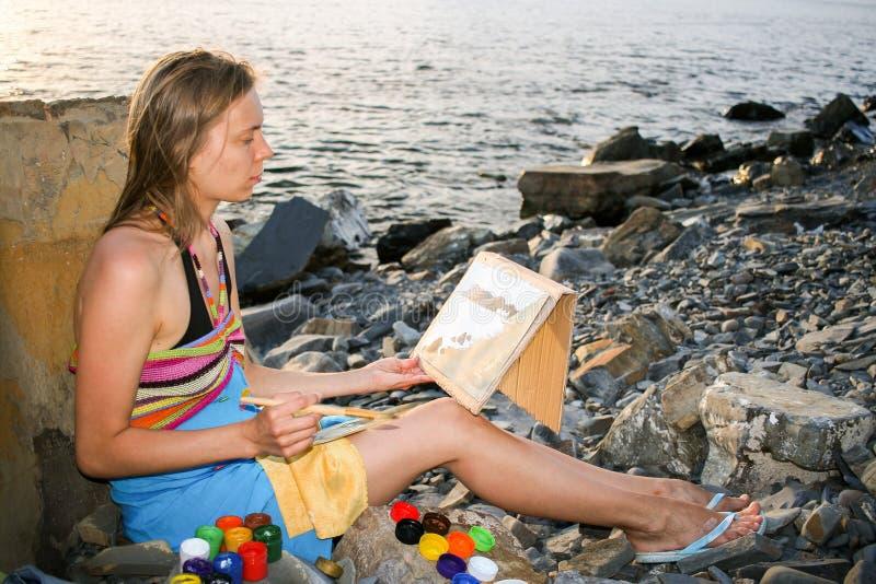 En ung flicka drar vid gouache på pappers- sammanträde på den steniga havsstranden på solnedgången arkivbild