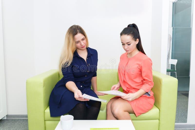 En ung flicka får rådgivning från en cosmetologist, bantar specialisten som sitter på en grön soffa arkivfoton