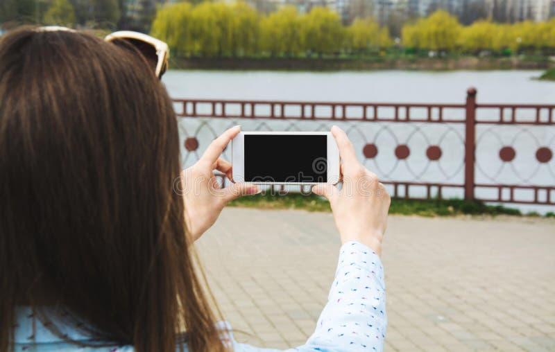 En ung flicka gör selfie i parkerar En flicka tar bilder av henne på en mobiltelefon i gatan arkivfoto
