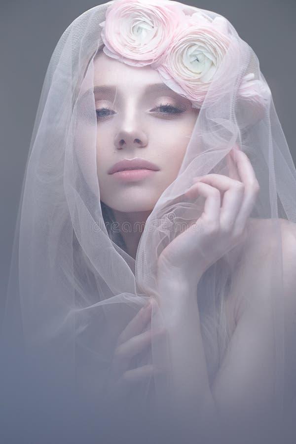 En ung flicka i bilden av en brud med en skyla på hennes framsida Härlig modell med en krans av blommor på hennes huvud arkivfoto