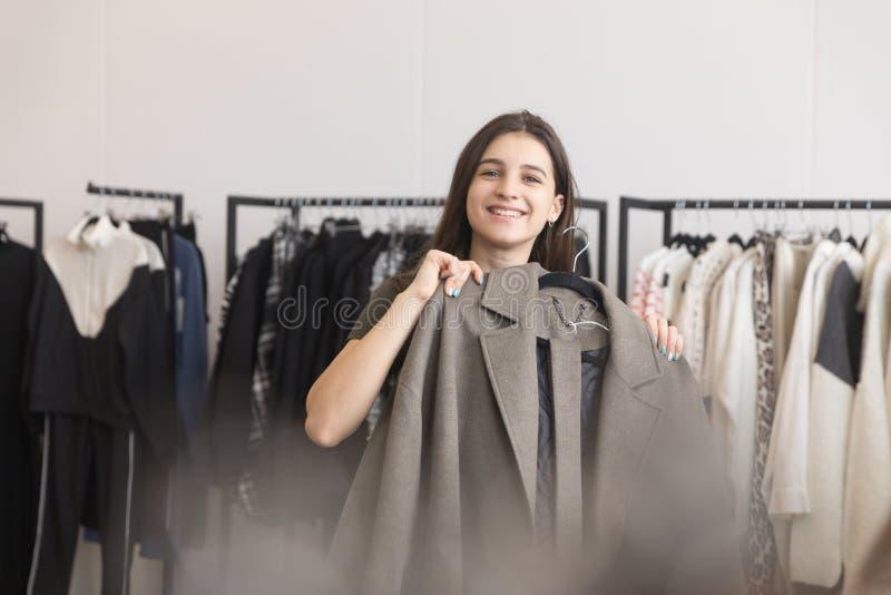 En ung flicka i ett bekläda lager väljer ett lag royaltyfri fotografi
