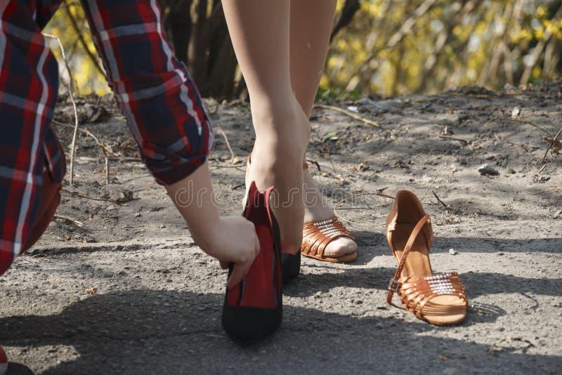 En ung flicka i gatan tar av hennes tillfälliga skor och sätter på feriekläder royaltyfri bild