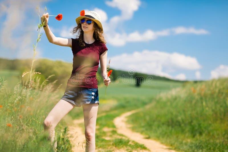 En ung flicka i hatt plockar blommor f?r en vallmo - vid vagnsv?gen arkivfoto