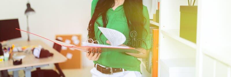 En ung flicka i kontoret rymmer en mapp med dokument royaltyfri bild