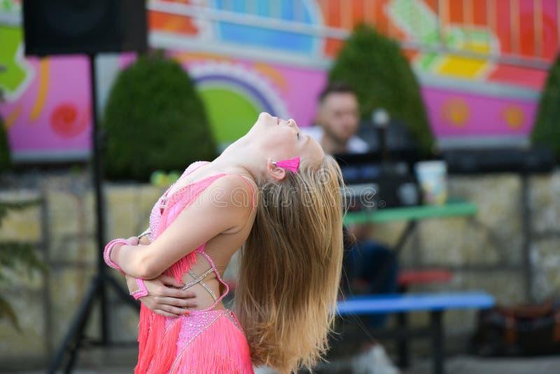 En ung flicka i rosa färger dansar Le dans Dansa i gatan I dräktdansen arkivbild
