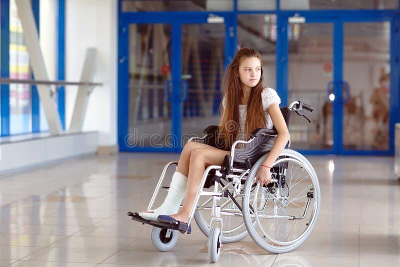 En ung flicka i en rullstol st?r i korridoren av sjukhuset royaltyfria foton
