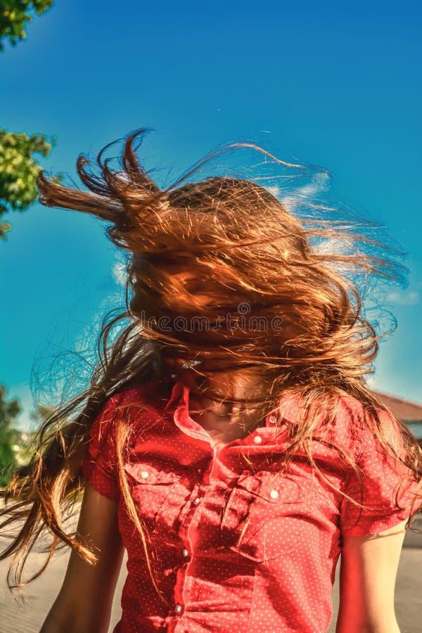 En ung flicka i solljuset med långt hår som fladdrar i vinden arkivfoto