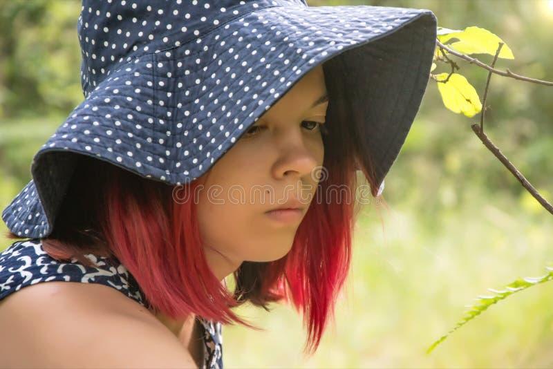 En ung flicka i en stor hatt samlar bär i träkorgar i sommarskogen som samlar gåvor av skogen arkivfoto