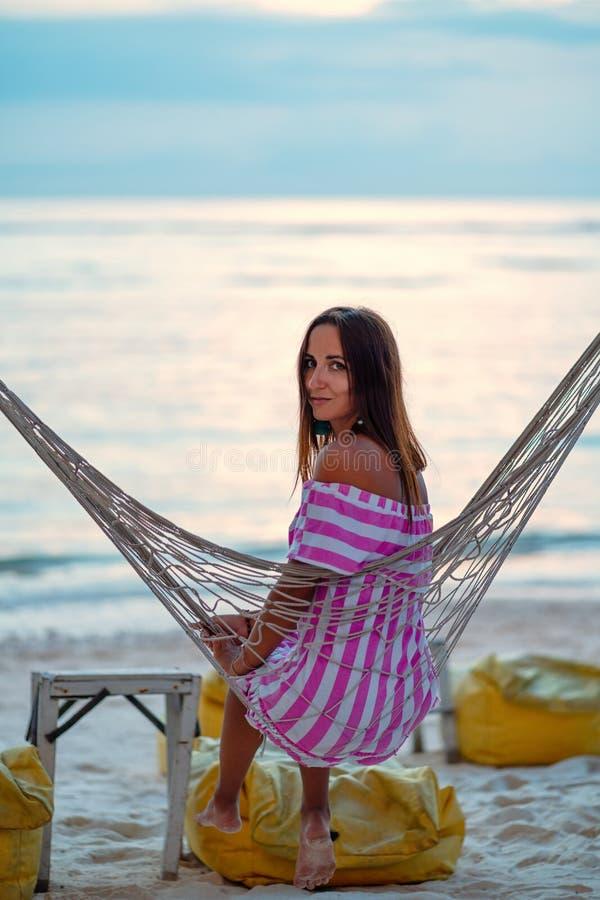 En ung flicka i sundress som vilar i en hängmatta på stranden Sikten från baksidan fotografering för bildbyråer