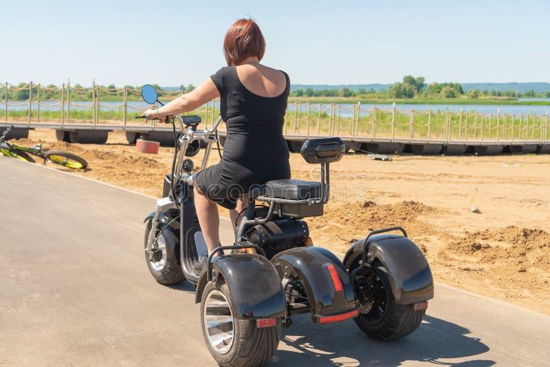 En ung flicka i en svart klänning med rött hår som kör hennes tre-rullade elektriska motorcykel längs stranden på en solig dag royaltyfri bild