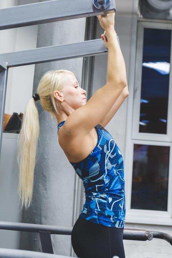 En ung flicka kopplas in i idrottshallen att underhålla hälsa och slankhet Flickan uppsätta som mål på det ideala diagramet av kr arkivbild