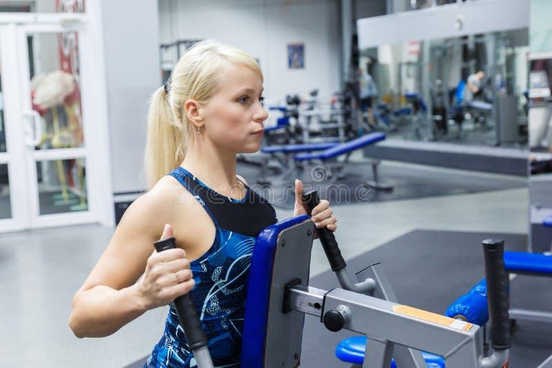 En ung flicka kopplas in i idrottshallen att underhålla hälsa och slankhet Flickan uppsätta som mål på det ideala diagramet av kr arkivfoto