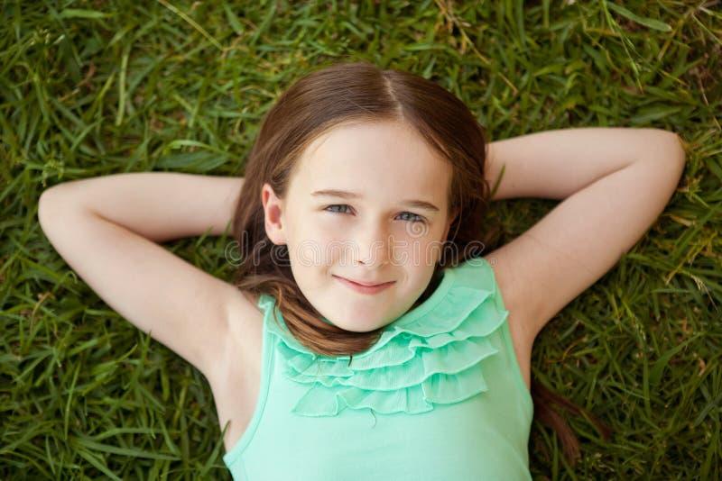 En ung flicka ligger på henne tillbaka på gräset som ser upp arkivfoton