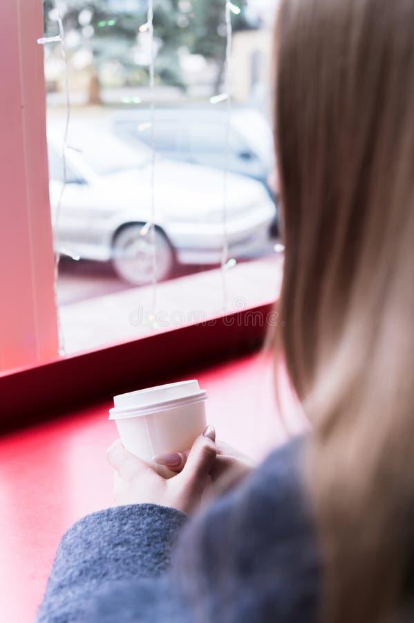 En ung flicka med ett exponeringsglas i hennes händer ser ut fönstret Närbild fotografering för bildbyråer
