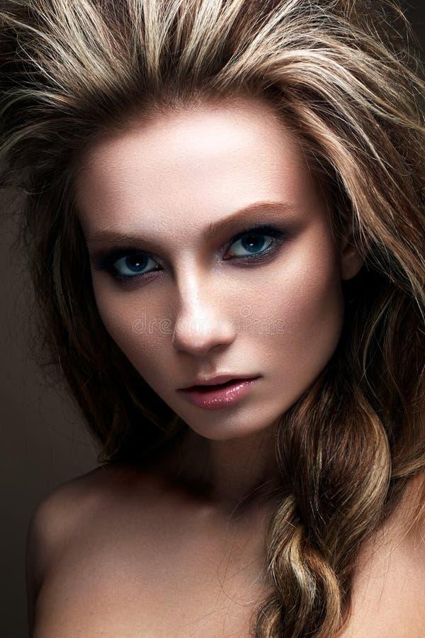 En ung flicka med ett idérikt ljust smink och en frodig frisyr Härlig modell med smokies Skönhet av framsidan royaltyfria bilder