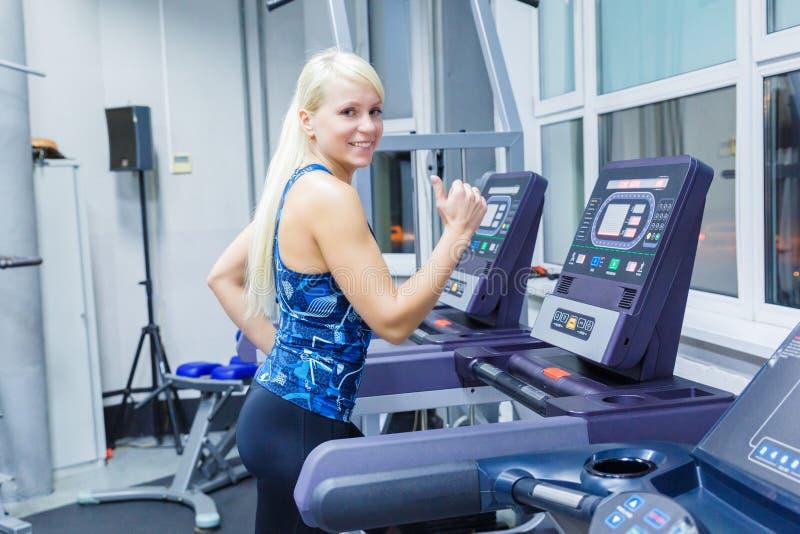 En ung flicka med ett leende som kör på trampkvarnen i idrottshallen royaltyfri fotografi