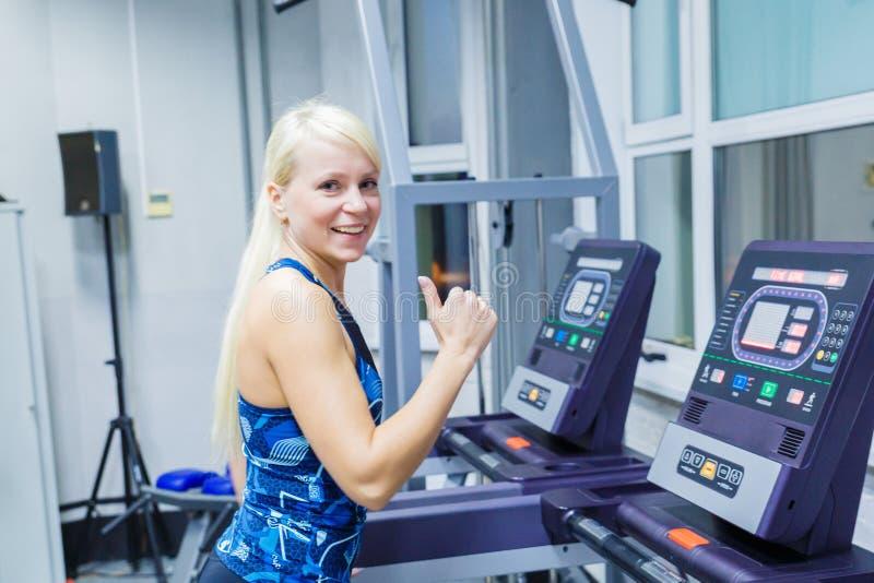 En ung flicka med ett leende som kör på trampkvarnen i idrottshallen royaltyfria foton