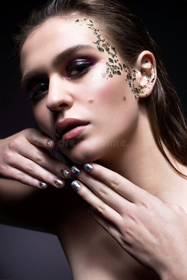 En ung flicka med flödande hår och smokeys Härlig modell med idérik och ljus konstmakeup och manikyr från folie arkivfoto