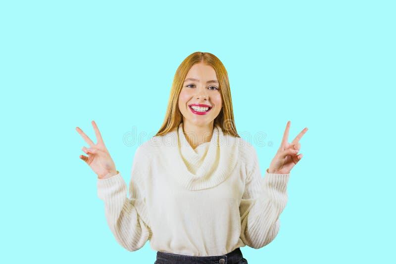 En ung flicka med långa röda hårshower pissar med båda händer som rymmer dem upp att le på en isolerad bakgrund fotografering för bildbyråer