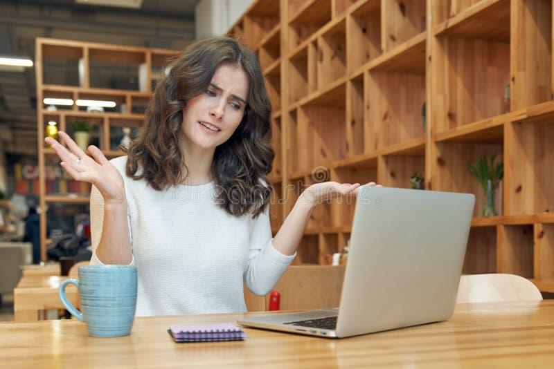 En ung flicka med långt sammanträde för lockigt hår i ett kafé med en lapto fotografering för bildbyråer