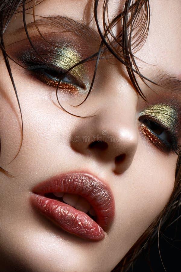 En ung flicka med ljus idérik makeup och gör perfekt hud Härlig modell med vått hår på framsida arkivbilder