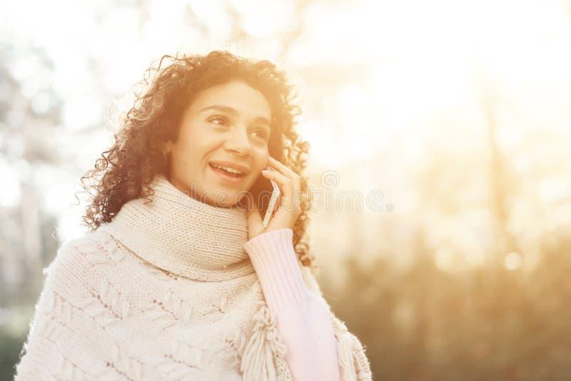 En ung flicka med lockigt hår poserar i den öppna luften på en solig dag royaltyfria foton