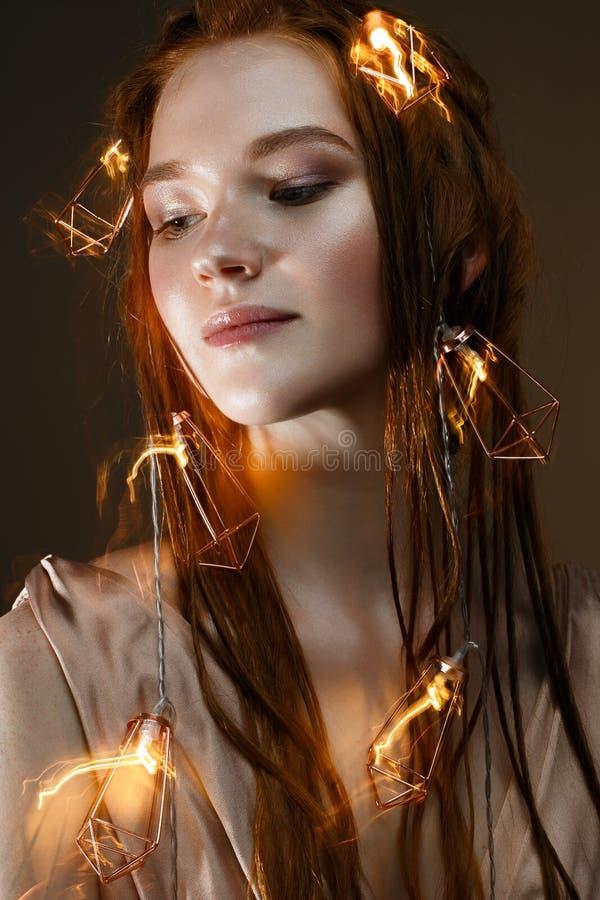 En ung flicka med rött hår och med en lysande girland Härlig modell med glänsande kulor och ljus Försiktig makeup fotografering för bildbyråer